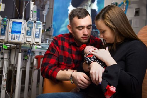Parents holding infant in a hospital setting