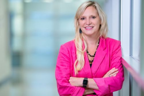 Researcher wearing bright pink jacket smiles at camera.