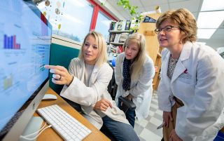 Image of people in white coats looking at a screen