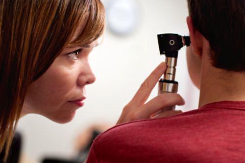 اختصاصي أبحاث السمع يفحص طفلاً مريضًا بالسرطان.