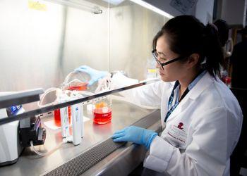 Female researcher in lab pouring liquid