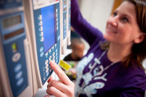 Enfermero ajusta las configuraciones para un paciente de cáncer pediátrico en la unidad de cuidados intensivos