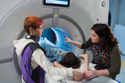 Pediatric cancer patient enters CT with Child Life Specialist offering explanations and mom standing near.
