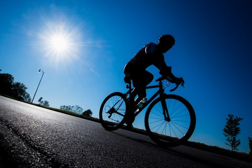 This picture shows a cyclist on a road bike wearing a helmet under a blue sky with a bright sun.