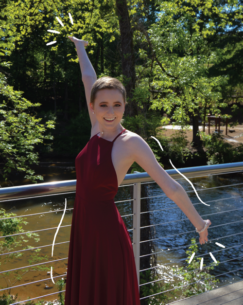 Elizabeth standing on a bridge with her arms spread apart.