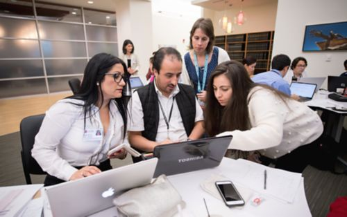 Group of Master's students looking at laptop