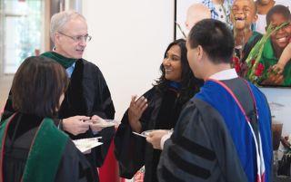 Four people in academic regalia talking