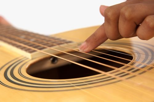 A patient's hand touches guitar strings