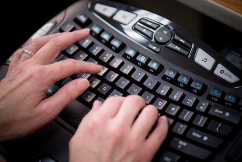 Two hands typing on a computer keyboard.