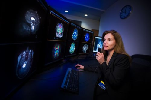 Radiologist sits at desk and reviews brain scans on multiple screens.