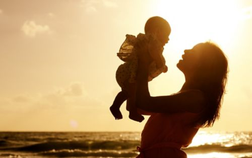 Mother holding child on beach at sunset