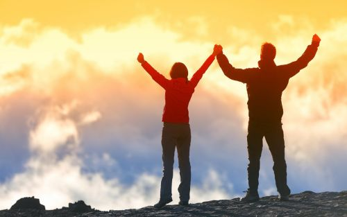 image of two people with arms raised