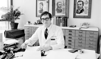 Walter Hughes sits at a desk early in his career