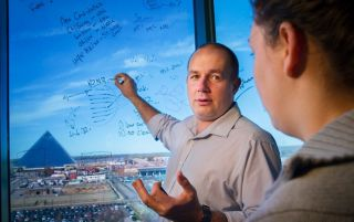 Image of man drawing formulas on window