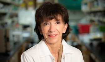 Martine Roussel, PhD, stands for a portrait with her lab blurred out in the background.