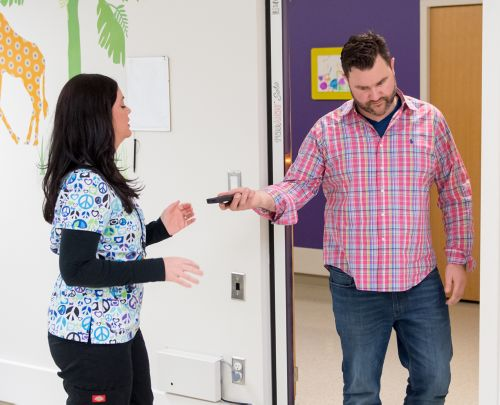 Pediatric cancer patient's father hands cell phone to MRI technologist after metal detector scan.