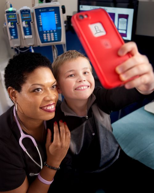 nurse and young pediatric cancer patient taking a selfie together
