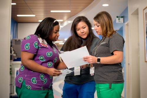 Three nurses stand together in a hallway reviewed a pediatric cancer patient's chart.