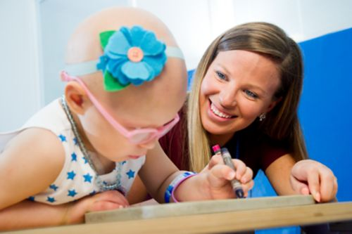 Occupational therapist smiles while working with very young pediatric cancer patient.