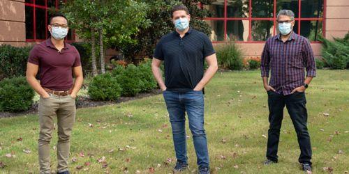 Three men wearing masks standing outside