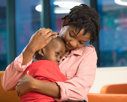 Pediatric cancer patient hugging mom