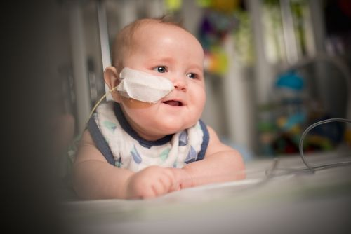 Infant with cancer smiles with NG tube visible