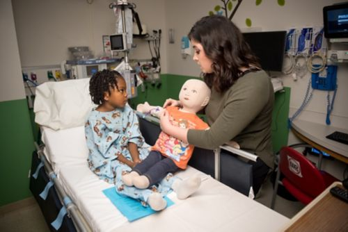 Child Life Specialist teaches young patient about a medical procedure.