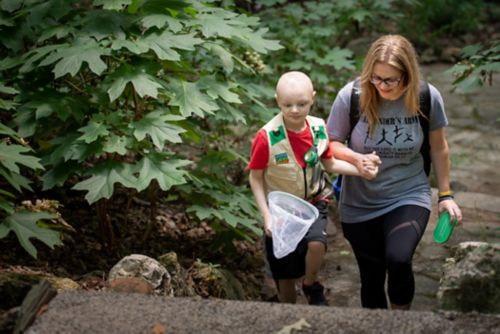 The stoma should not be painful once healed. Children should be able to do most regular activities. In this photo, a child with a G tube walks along a trail with his mom looking for insects.