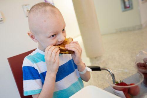 ساعد الأطفال في التخطيط للأكل في الأوقات التي يشعرون فيها بالتحسن. تعرض الصورة طفلاً مريضًا بالسرطان يأكل شطيرة من الجبن المحمّصة في كافتيريا المستشفى.