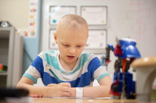 Haga un plan para la escuela al principio del tratamiento y reevalúelo regularmente. En esta imagen, un joven paciente de cáncer está sentado trabajando en las tareas escolares.