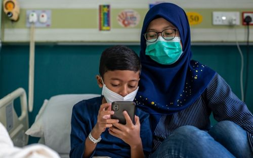Boy and mother wearing face masks, looking at phone while sitting on a hospital bed.