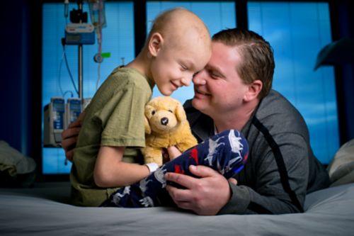 Une jeune patiente atteinte d'un cancer sur son lit d'hôpital sourit, câline un chien en peluche tout en étant front à front avec son père, qui a un genou à terre et se penche sur le lit.