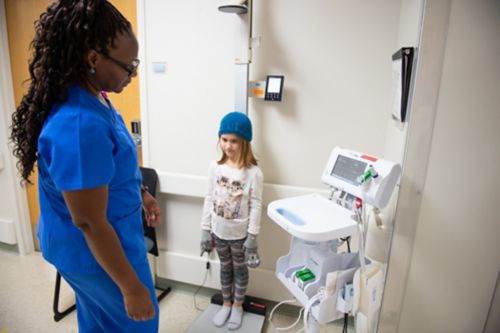 Childhood cancer patients at risk for developing growth hormone deficiency should have an exam that includes measurement of height and weight every six months until growth is completed. In this image, cancer center staff measures a survivor's weight.