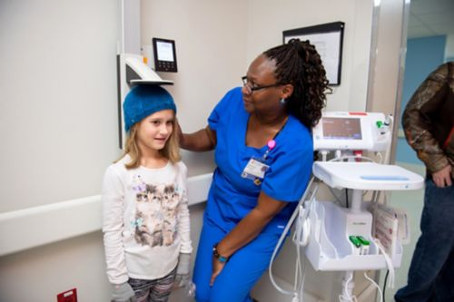 Childhood cancer survivors may develop growth problems as a result of certain cancer treatments. In this image, cancer center staff measures a survivor's height.