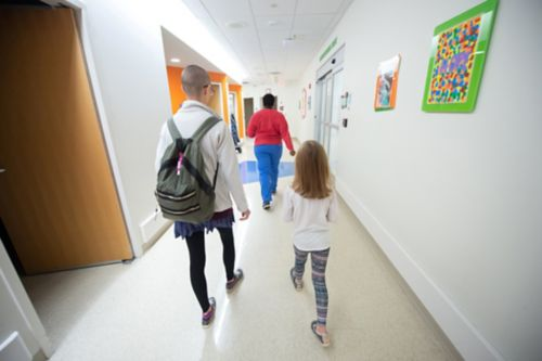 Transitioning off childhood cancer treatment can be a period of uncertainty and anxiety for survivors. In this image, a childhood cancer survivor walks down a hospital hallway behind hospital staff.