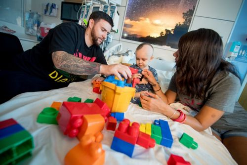 This photo shows a mom and a dad playing with their child on his hospital bed.