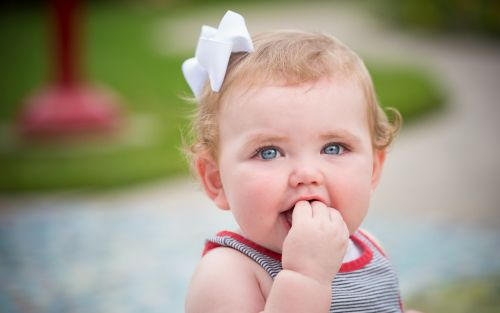 Young child with a bow in her hair and holding her fingers in her mouth.