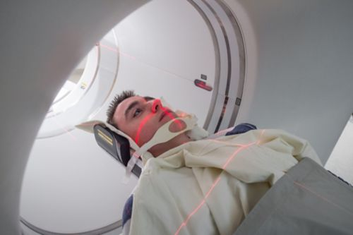 Young male cancer patient is beginning PET scan, red lights visible on his face.