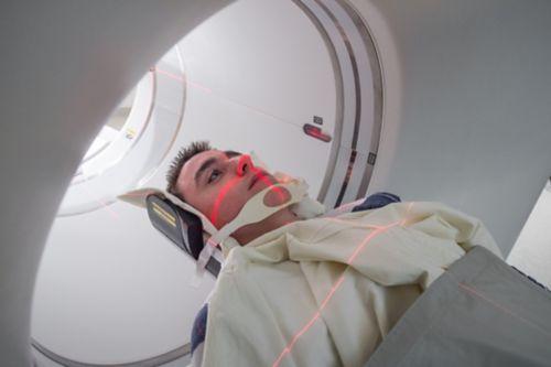 युवा पुरुष कैंसर रोगी का पैट स्कैन होते हुए, लाल बत्ती उसके चेहरे पर दिखाई दे रही है।