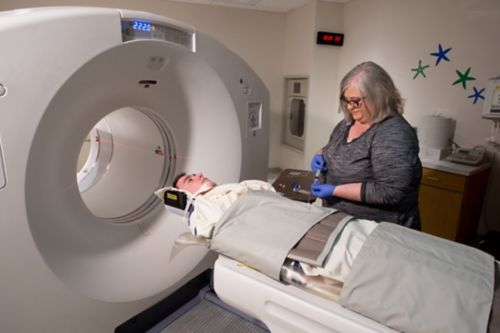 Young male cancer patient receives radioactive tracer while in position for PET scan.