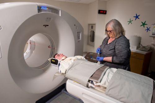पैट स्कैन कराने के लिए तैयार युवा पुरुष कैंसर रोगी रेडियोएक्टिव ट्रेसर लेता है।