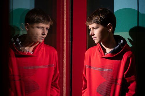 Un paciente con una camiseta roja mirando su reflejo en una ventana.