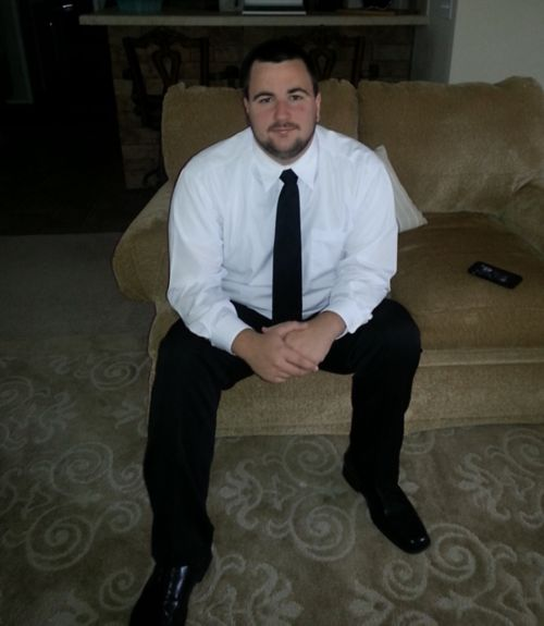 Patient sitting on a couch wearing a white shirt, black tie, and black pants.