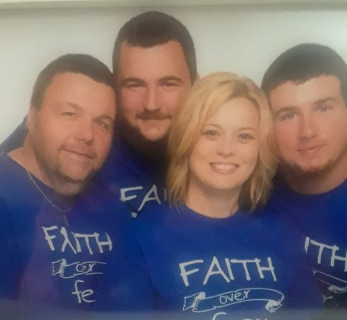 "Patient and family, four people total, wearing purple t-shirts that say ""Faith Over Fear."""