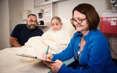 正在填写表格的小儿肿瘤科社会工作者、躺在医院病床上的患儿及其父亲
