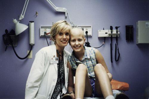 La paciente sentada en una sala de examinación con un miembro del equipo de atención médica.