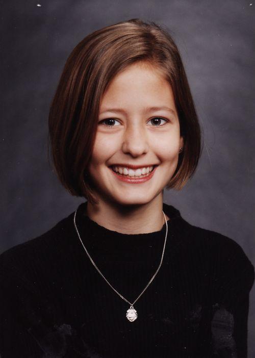 Retrato de la paciente usando un suéter negro y un collar, con el cabello suelto hasta la barbilla.
