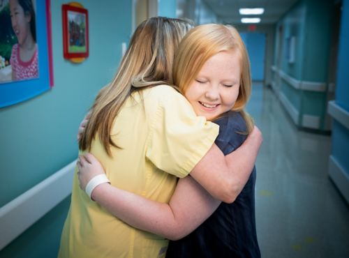 患者及其家人应该与医疗团队成员保持健康的关系界限。在这张图片中,一名医疗团队成员正在拥抱一名患儿。