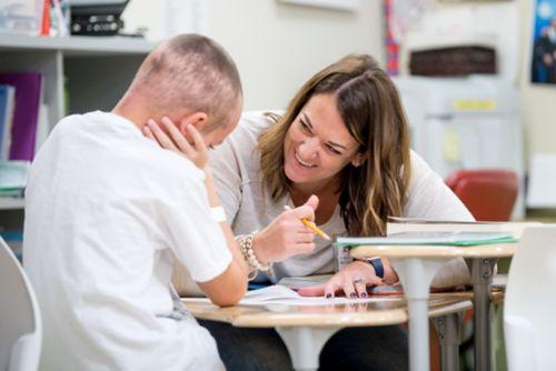 Paciente con cáncer pediátrico trabaja con un maestro en un entorno de clase.