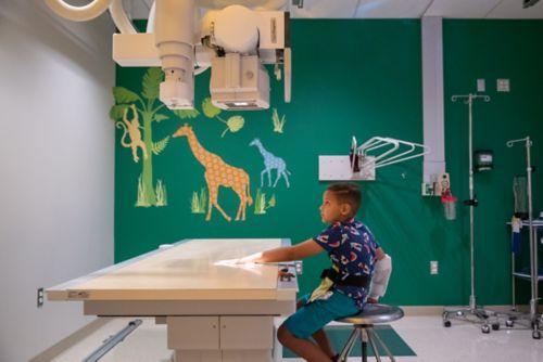 Paciente con cáncer pediátrico recostado en la camilla mientras un especialista en vida infantil le muestra un iPad y el técnico de rayosX ubica la máquina para realizar una prueba de rayosX en el abdomen.